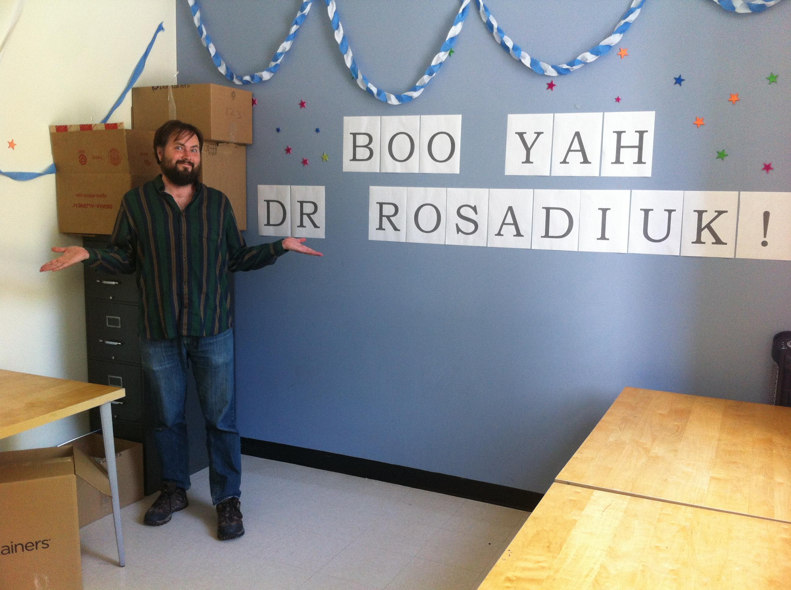 "Dr. Rosadiuk shrugging next to a celebratory sign on a wall saying ""Boo yah Dr. Rosadiuk!"""